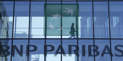 File picture shows a man silhouetted as he walks behind the logo of BNP Paribas in a building in Issy-les-Moulineaux